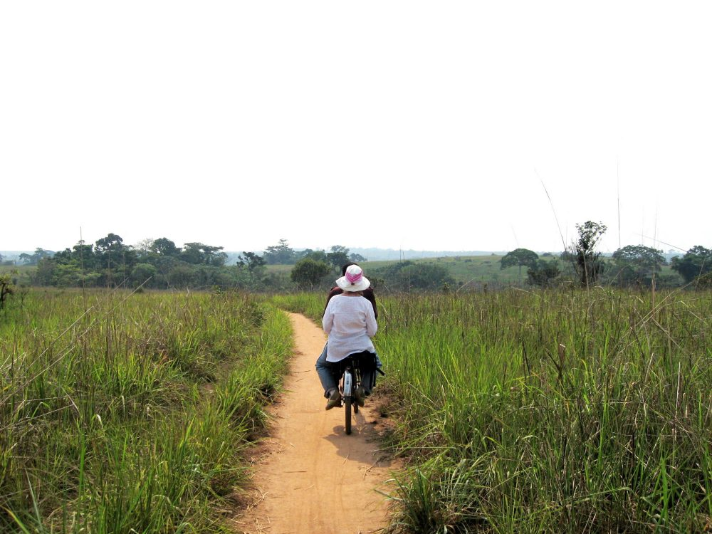 In this 2006 photo, Beth Duff-Brown hitches a ride on the back of a bicycle on her way back to Kamponde, the Congolese village where she was a Peace Corps. (Claude Kamanga Mutdon/AP)