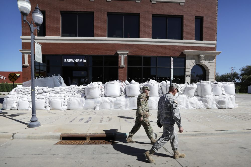 Iowa National Guard members walk past a local business covered in sandbags, Monday, Sept. 26, 2016, in Cedar Rapids, Iowa. (Charlie Neibergall/AP)