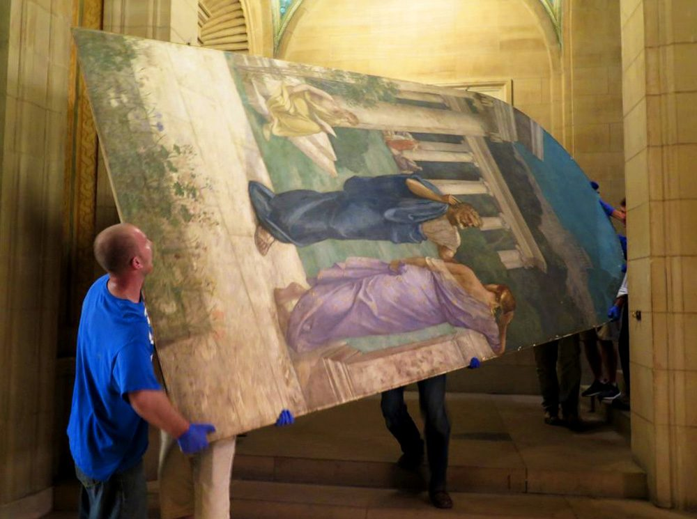 "Gloved workers slowly and carefully move the ""Philosophy"" panel, created by 19th century French muralist Pierre Puvis de Chavannes, in the Boston Public Library. (Andrea Shea/WBUR)"