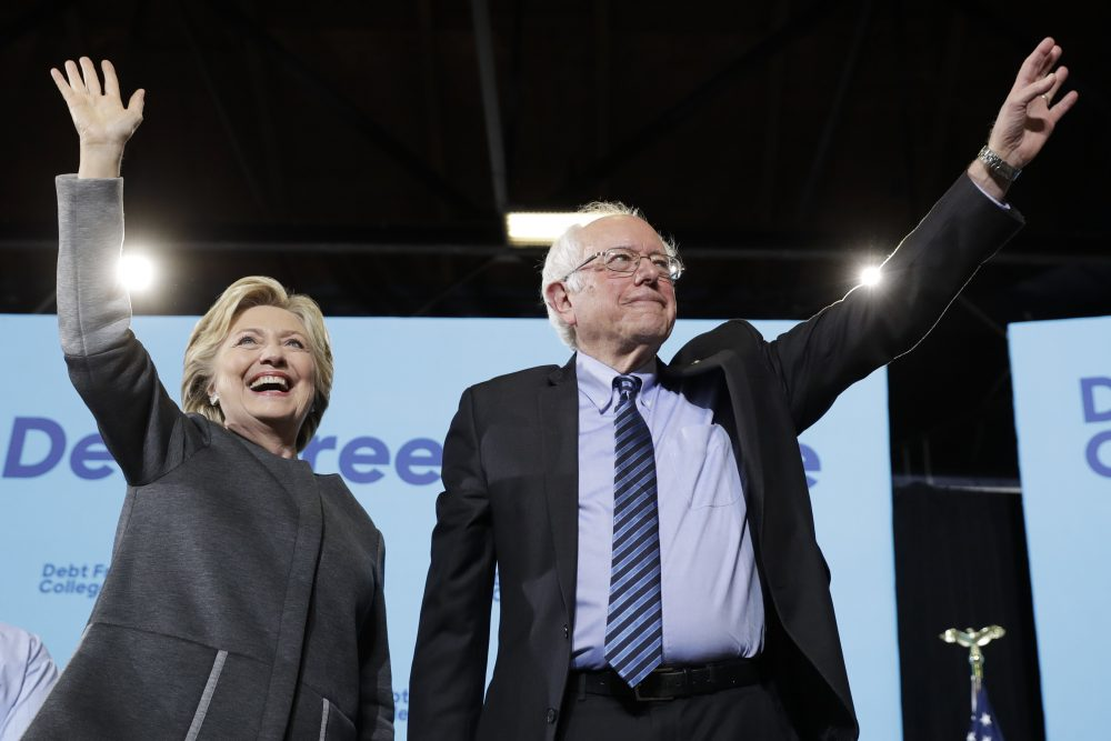 Democratic presidential candidate Hillary Clinton and Sen. Bernie Sanders, I-Vt., take the stage during a campaign stop at the University Of New Hampshire in Durham on Wednesday. (Matt Rourke/AP)