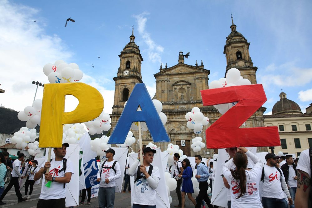 """People hold up letters that form the word """"Peace"""" in Spanish during a gathering at Bolivar square in Bogota, Colombia, Monday, Sept. 26, 2016. (Jennifer Alarcon/AP)"""