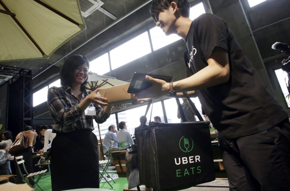 A delivery man brings ordered food during a press conference of UberEats, which opens in Tokyo on Thursday, on Wednesday, Sept. 28, 2016. (Eugene Hoshiko/AP)