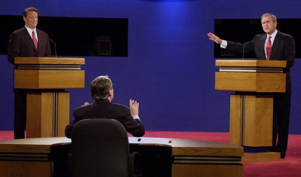 Moderator Jim Lehrer speaking to George W. Bush and Vice President Al Gore at the first presidential debate in October 2000 at the University of Massachusetts in Boston. (Ron Edmonds/AP)