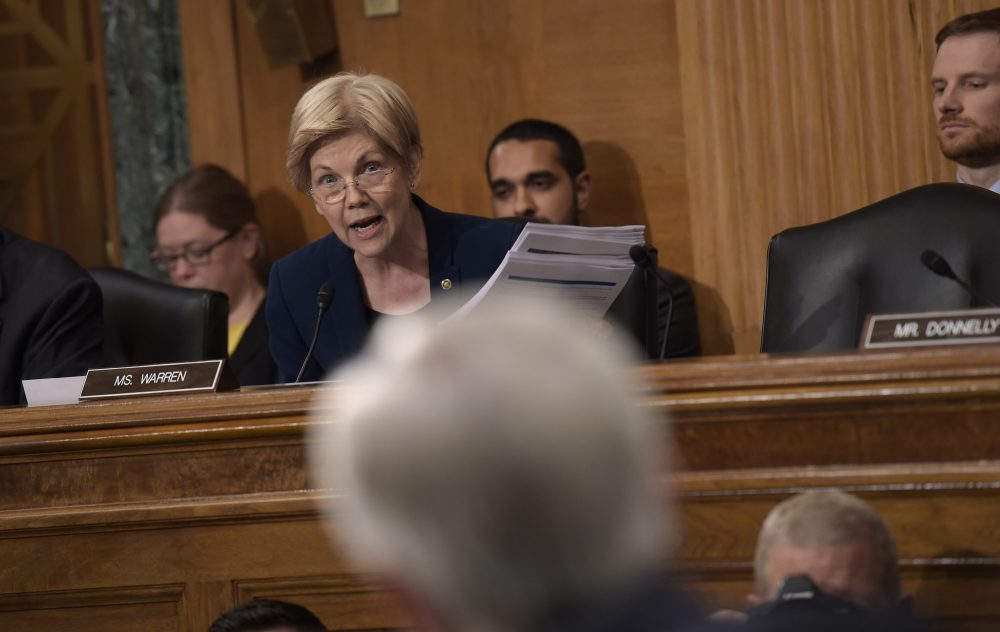 Senate Banking Committee member Elizabeth Warren holds up transcripts of earnings calls as she questions Wells Fargo CEO John Stumpf on Capitol Hill Tuesday. (Susan Walsh/AP)