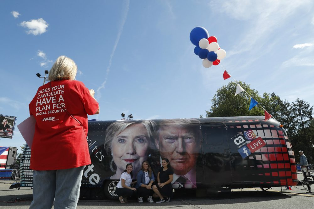 People pose for a photo kneeling near a bus adorned with photos of candidates Hillary Clinton and Donald Trump before the presidential debate at Hofstra University in Hempstead, N.Y., Monday, Sept. 26, 2016. (Mary Altaffer/AP)