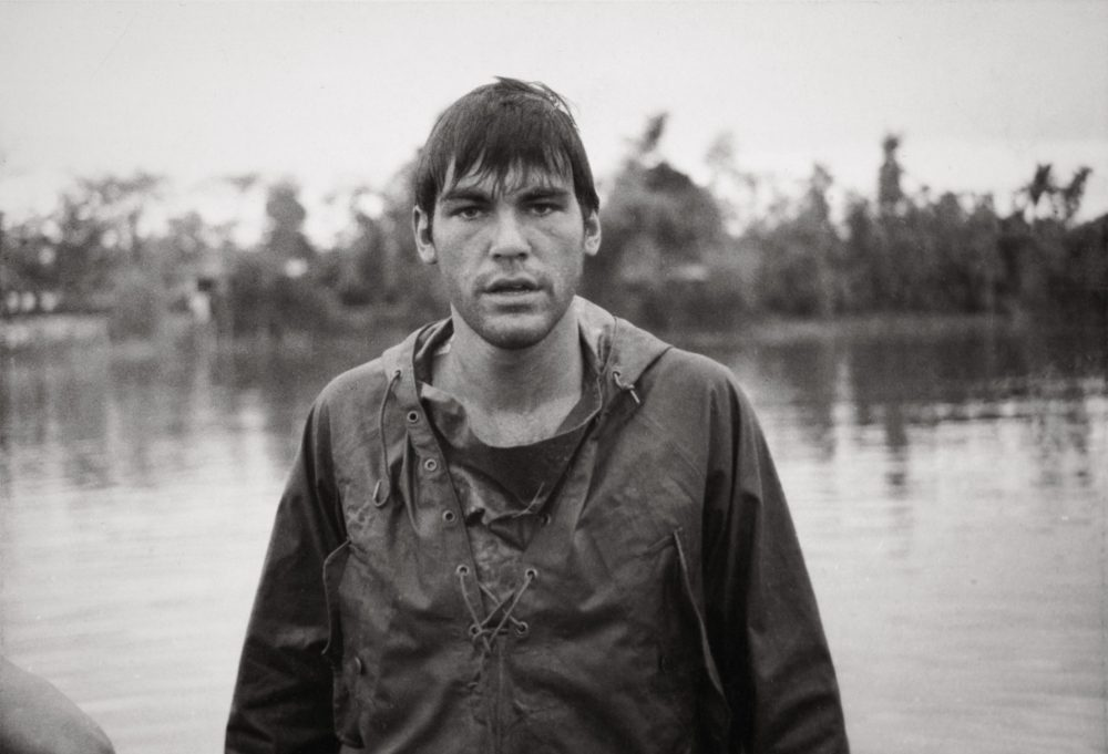 Soaking wet in a poncho, Stone is pictured coming off an APC (Armored Personnel Carrier) and crossing a river near a demilitarized zone in the First Cavalry Division, 1968. (Courtesy of Oliver Stone and Ixtlan Productions)