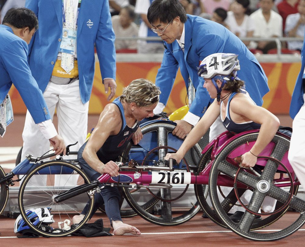 American Cheri Blauwet, center, is helped by officials while her teammate Amanda McGrory looks on after they crashed on the last lap of the Women's 5,000 meter T54 final during the Beijing Paralympic Games, Sept. 8, 2008. (AP Photo/Andy Wong)