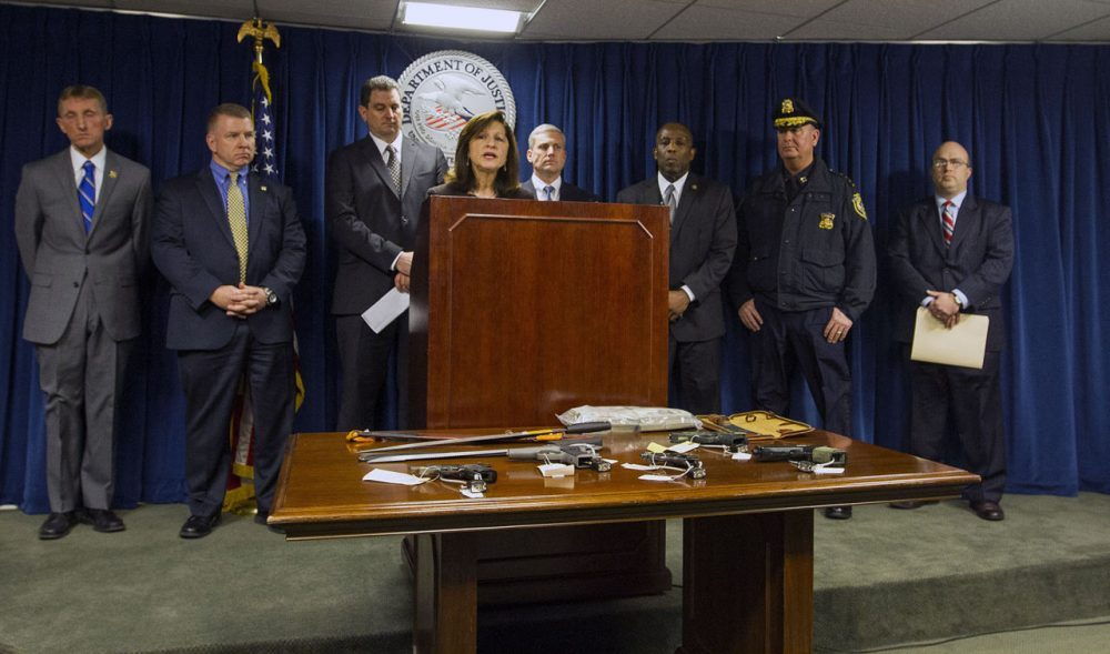 U.S. Attorney Carmen Ortiz, standing among other law enforcement officials, announces in January 2016 the indictment of suspects believed to be members of the violent Salvadoran street gang MS-13. (Joe Difazio for WBUR)