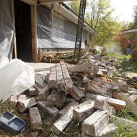 This Nov. 6, 2011 file photo, Chad Devereaux works to clear up bricks that fell from three sides of his in-laws' home in Sparks, Okla, after two earthquakes hit the area in less than 24 hours. (Sue Ogrocki/AP)