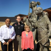 "Chickasaw tribal elders Jerry Imotichey (left) and Hannah Pitmon (right) stand with Joshua Hinson (middle), director of the Department of Chickasaw Language, in front of ""The Arrival"" statue at the Chickasaw Cultural Center in Sulphur, Okla. (Karyn Miller-Medzon/Here & Now)"