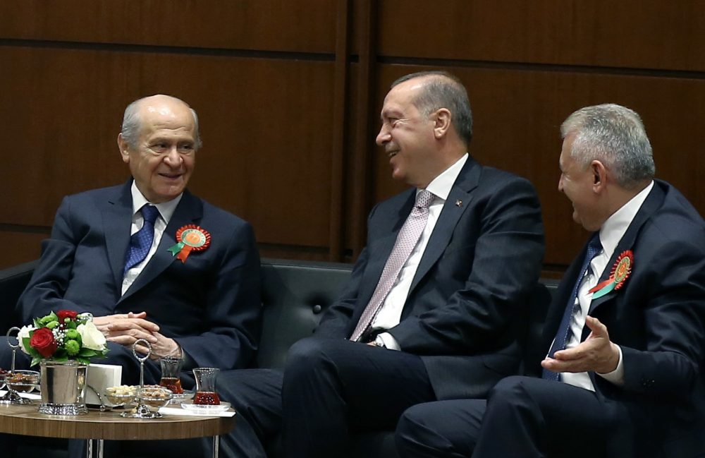Turkey's President Recep Tayyip Erdogan, center, Prime Minister Binali Yildirim, right, and opposition Nationalist Movement Party leader Devlet Bahceli speak before Erdogan addresses a gathering of judges and lawyers at his palace in Ankara, Turkey on Sept. 1. (Yasin Bulbul, Presidential Press Service, Pool via AP)