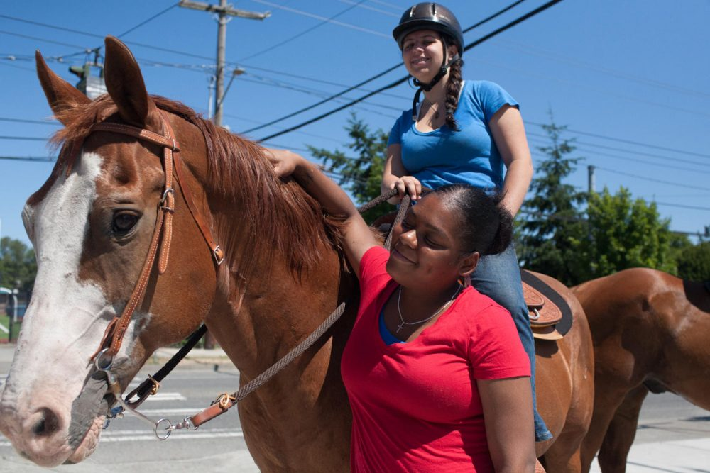 Riley Neiders and her horse Homer attract the attention of Rainier Beach resident Lamaya Barron. (Matt Mills McKnight/KUOW)