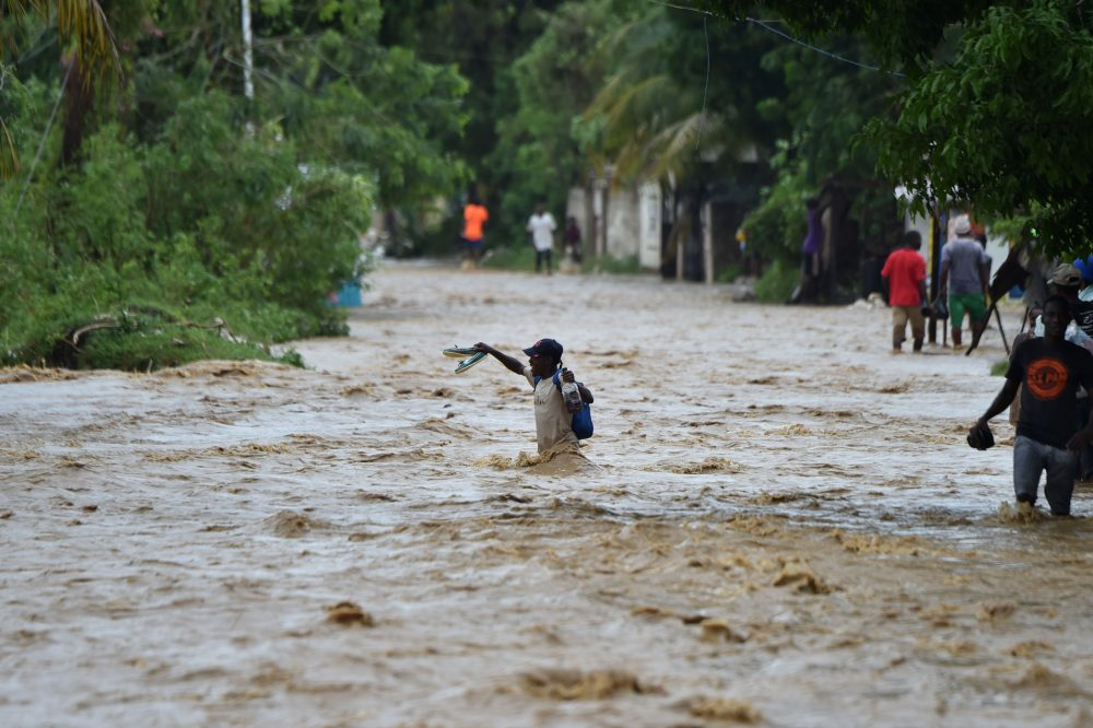 People try to cross the overflowing La Rouyonne river in the commune of Leogane, south of Port-au-Prince, in Haiti on Oct. 5, 2016. (Hector Retamal/AFP/Getty Images)