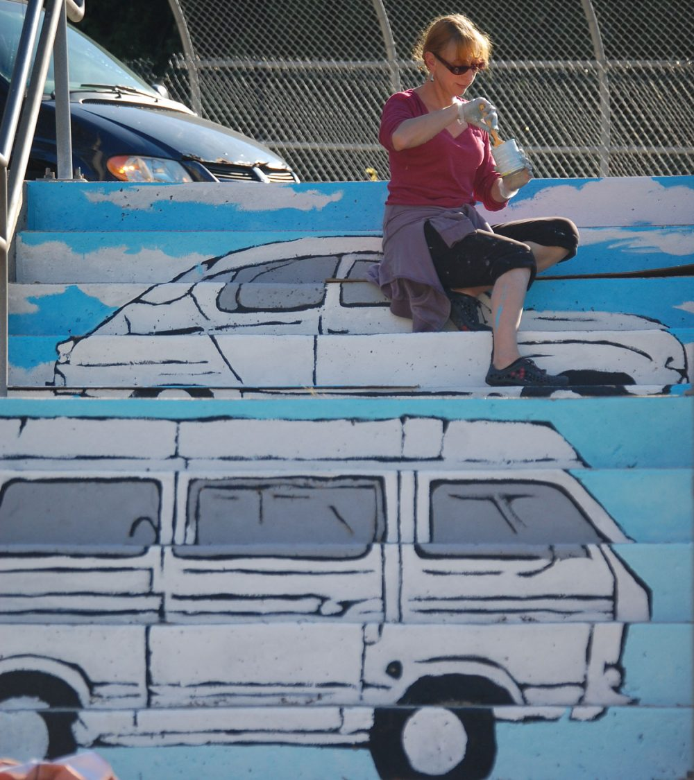 "Liz LaManche paints ""The Soul's Journey as a Series of Weird Old Automobiles"" in the park at the intersection of Pearl and Medford streets in Somerville. (Greg Cook)"