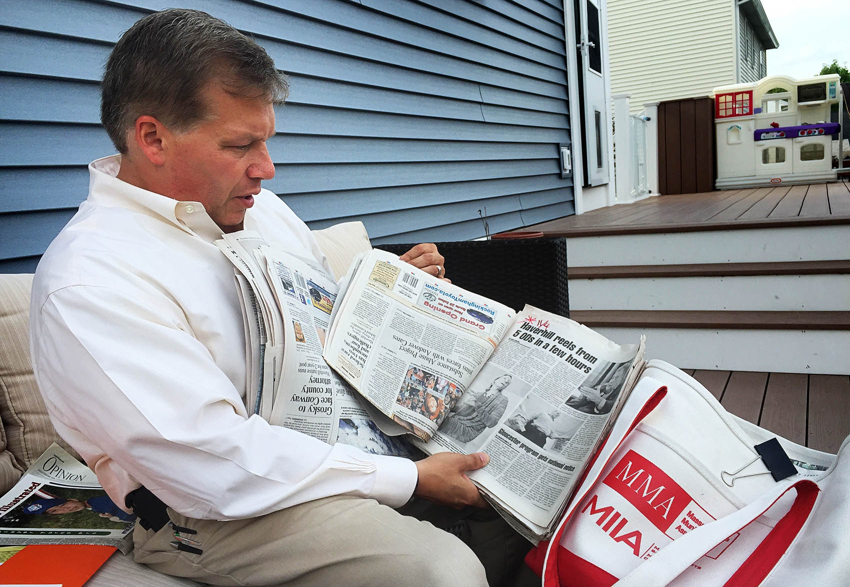 At his home in Haverhill, Colin LePage leafs through newspapers he shows to middle-schoolers to educate them about the dangers of drugs. (Martha Bebinger/WBUR)