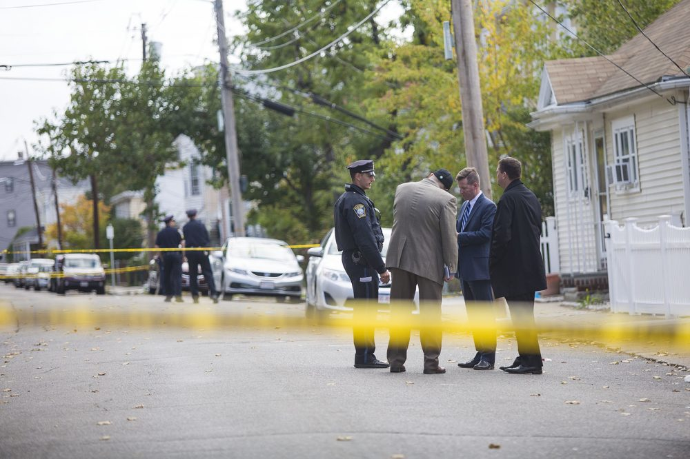 Boston police officers stand on Gladstone Street in East Boston Thursday morning after two cops were shot and injured Wednesday night. (Jesse Costa/WBUR)