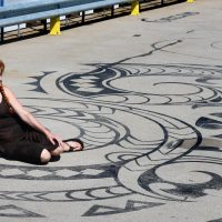"""Artist Liz LaManche sits on her """"Connected by Sea"""" installation on the dock of the East Boston Shipyard. (Amy Gorel for WBUR)"""