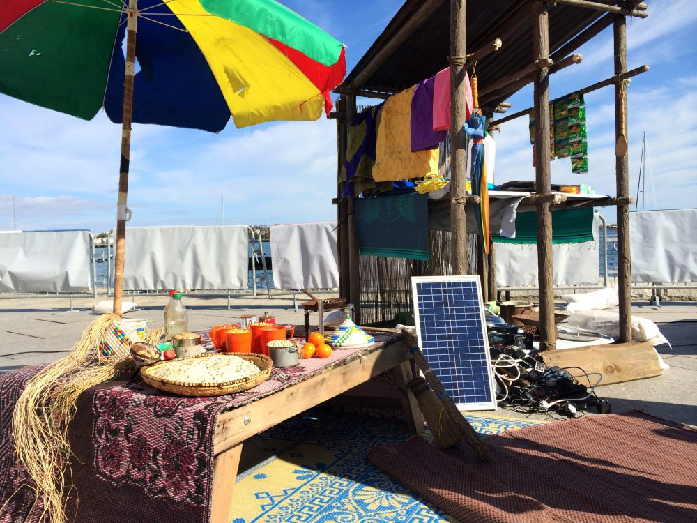 A makeshift market as seen, set up at Long Wharf in Boston. The market and charging stations are common scenes in refugee camps, the Doctors Without Borders volunteers say. (Qainat Khan for WBUR)