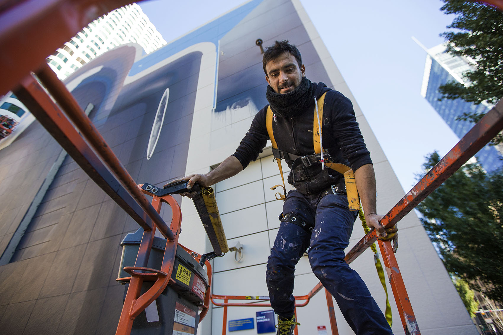 Iranian artist Mehdi Ghadyanloo climbs into a cherry picker as he works on the latest mural to go up on the Rose Kennedy Greenway in Dewey Square. (Jesse Costa/WBUR)