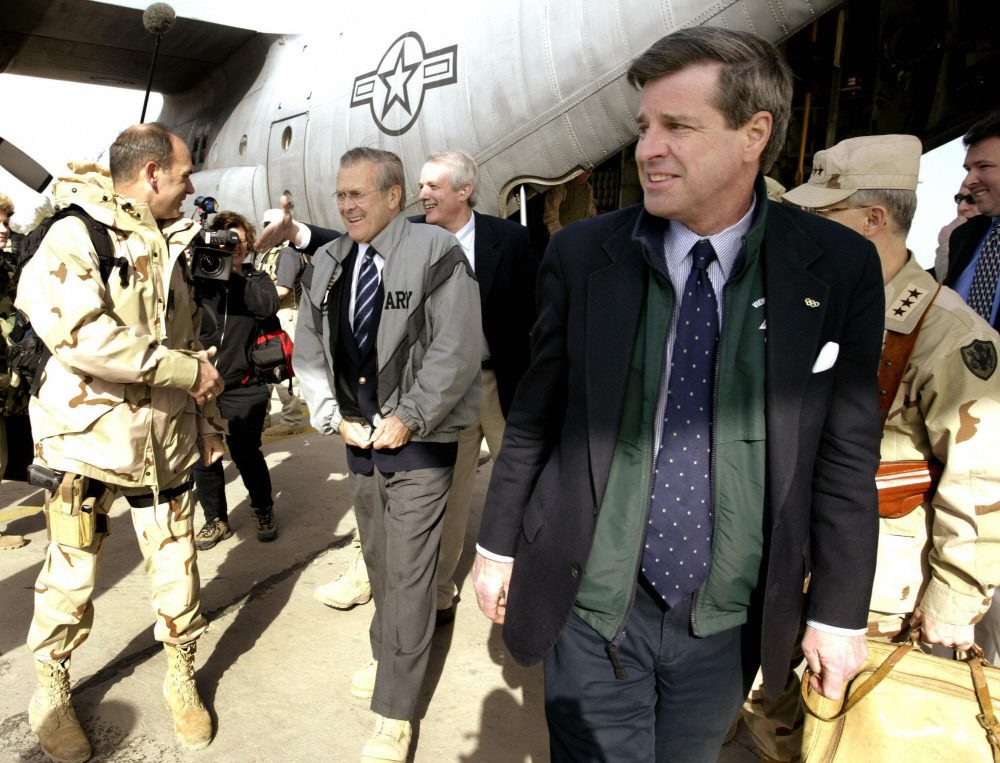 U.S. Defense Secretary Donald Rumsfeld, center, is received off a C-130 transport plane by Paul Bremer, right, the chief of the U.S.-led coalition authority in Iraq, on Feb. 23, 2004 at the Baghdad International Airport. (Jason Reed/AFP/Getty Images)
