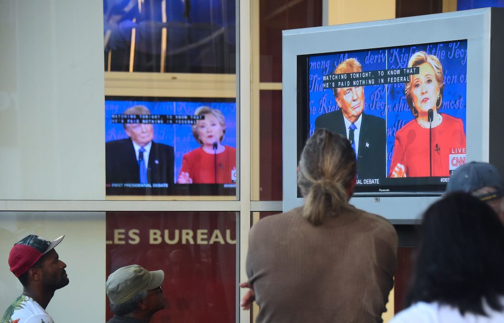 People gather to watch the first U.S. presidential debate between Hillary Clinton and Donald Trump, nominees for the Democratic and Republican parties respectively, on a television set in front of an office building in Hollywood, Calif., on Sept. 26, 2016. (Frederic J Brown/AFP/Getty Images)