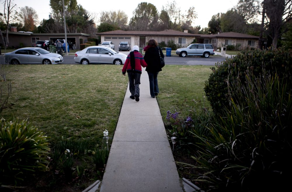 In this photo taken Dec. 22 2011, Evelyn Volk, right, walks with her mother Maria Koenig, who suffers from dementia, as they leave home for grocery shopping in the Woodland Hills section of Los Angeles. (Jae C. Hong/AP)
