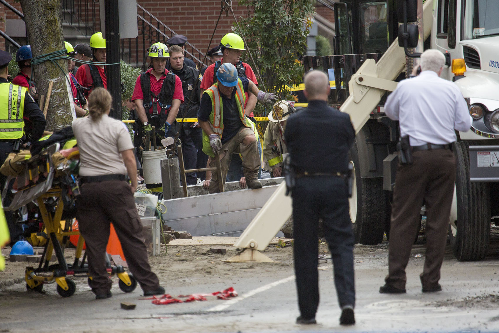 A response team works to recover the bodies of two men who were trapped in a trench during a water main break on Dartmouth Street in Boston's South End Friday. (Jesse Costa/WBUR)