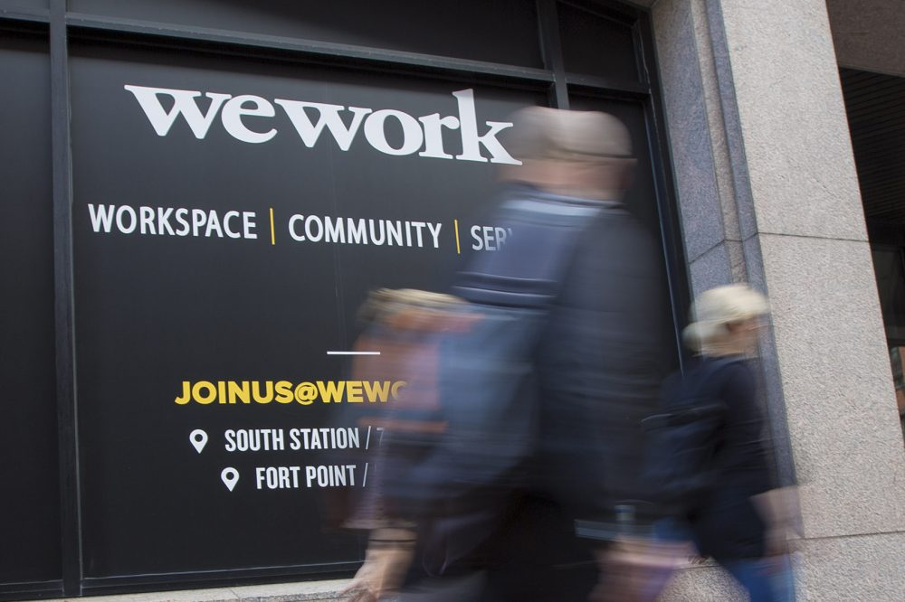 People walk by the office of WeWork at South Station on Beach Street. (Jesse Costa/WBUR)