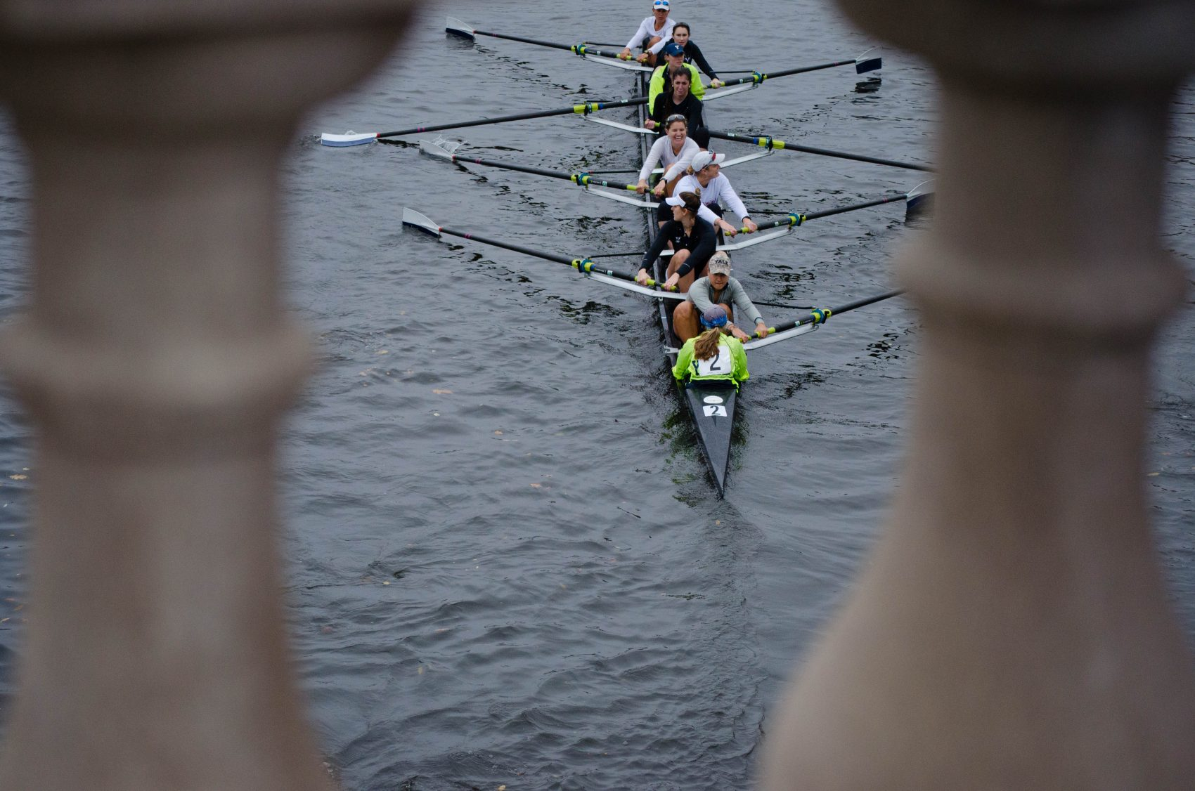 Boats pass under the Weeks Footbridge on their way to the starting line for the Head of the Charles. (Elizabeth Gillis/WBUR)