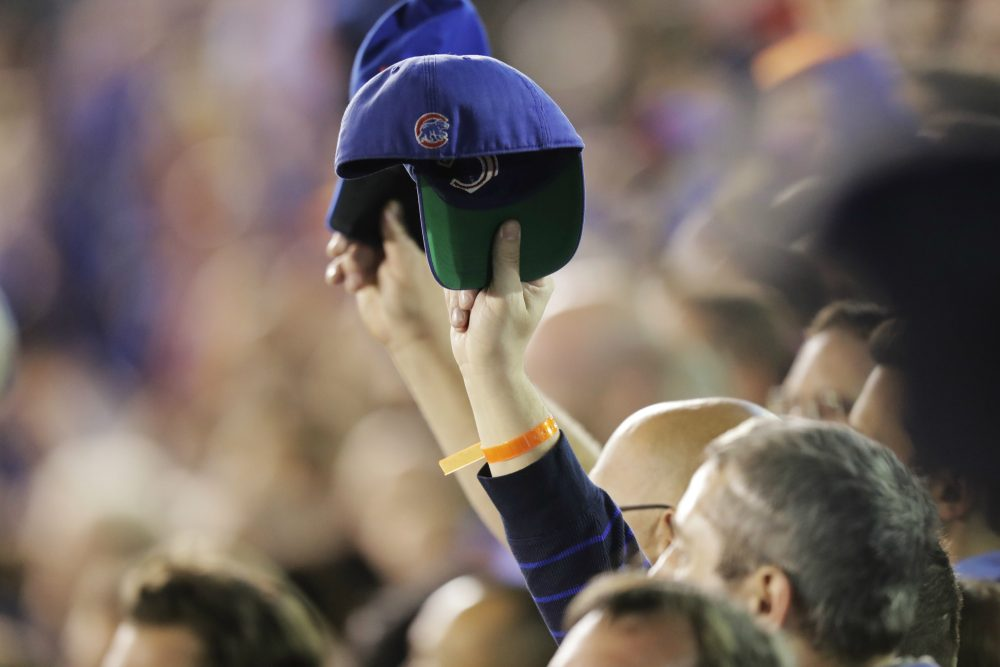 Fans raise their caps during the national anthem before Game 6 of the National League baseball championship series between the Chicago Cubs and the Los Angeles Dodgers, Saturday, Oct. 22, 2016, in Chicago. (Charles Rex Arbogast/AP)