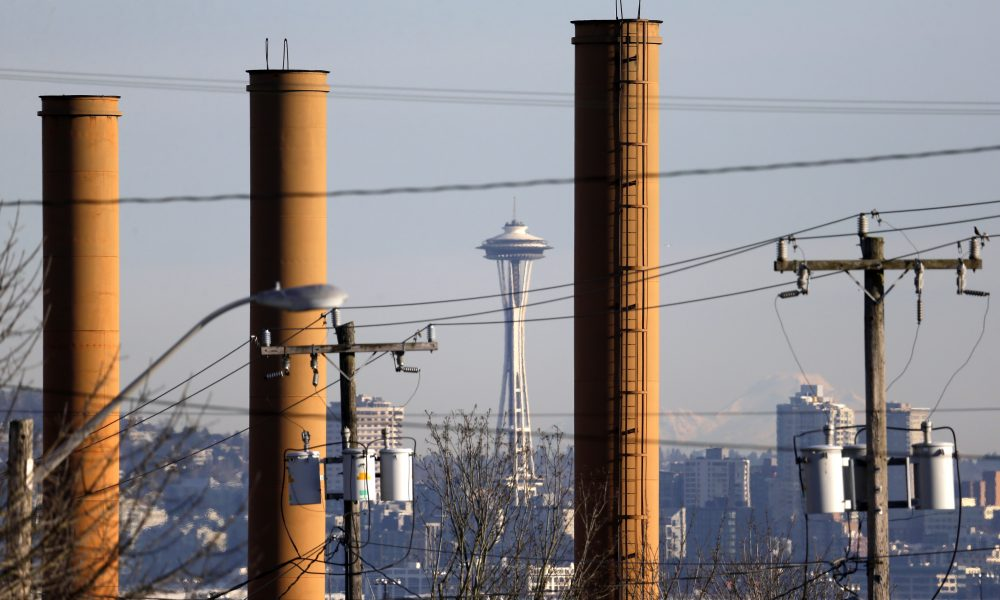 In this Thursday, Feb. 25, 2016 photo, the Space Needle is seen in view of still standing but now defunct stacks at the Nucor Steel plant in Seattle. The plant is among those likely to be affected if Washington state becomes the first in the nation to pass a tax on carbon pollution from fossil fuels such as coal, gasoline and natural gas. (Elaine Thompson/AP)