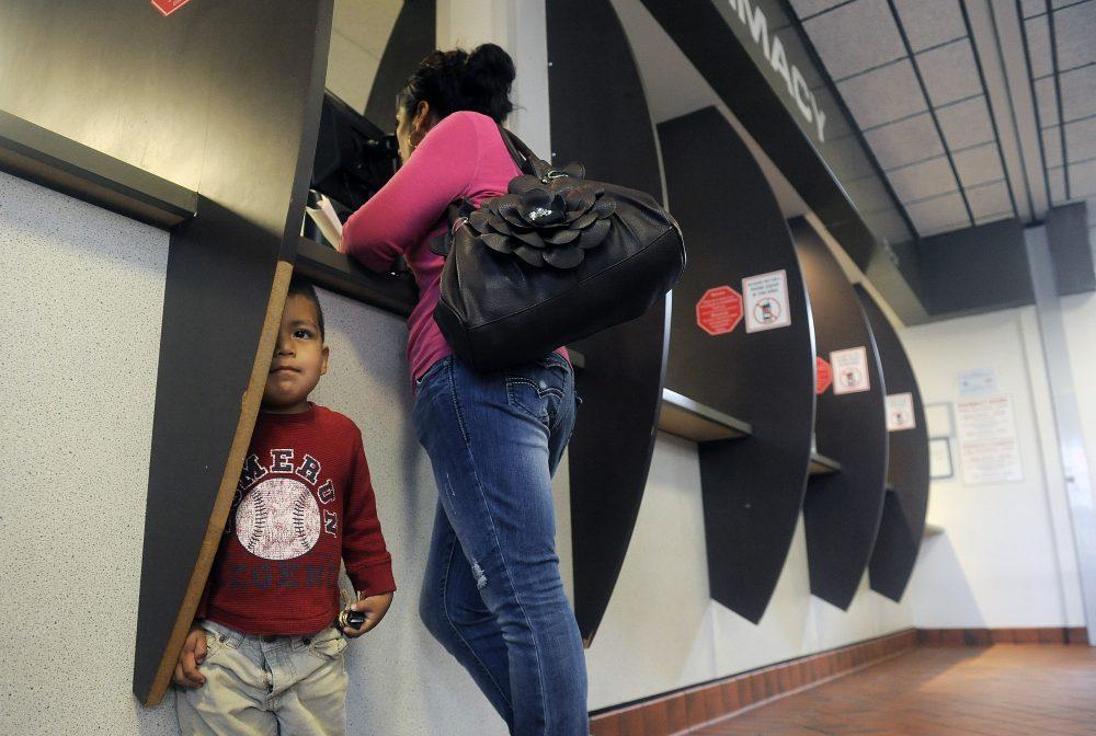 Laura Macias gets a prescription with her son Emiliano Macias at the Denver Health Westside Family Health Center on Oct. 1, 2013 in Denver. (Chris Schneider/Getty Images)