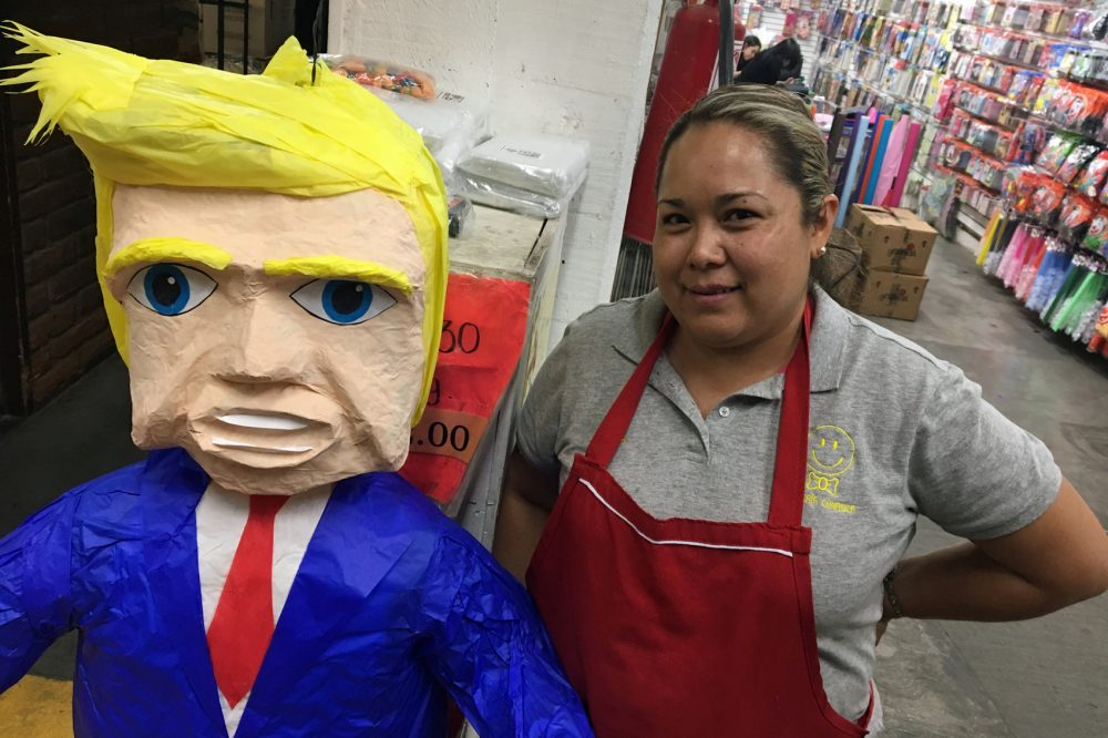 Alma Cruz shows off a Donald Trump piñata that's for sale at a party store in Nogales, Mexico. She says a customer in the District of Columbia has ordered several of them. (Valeria Fernandez for Here & Now)