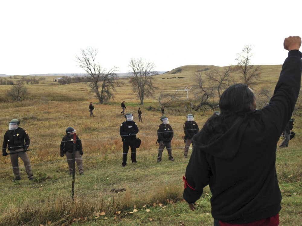 A Dakota Access pipeline protester defies law enforcement officers who are trying to force them from a camp on private land in the path of pipeline construction, Thursday, Oct. 27, 2016 near Cannon Ball, N.D. (James MacPherson/AP)
