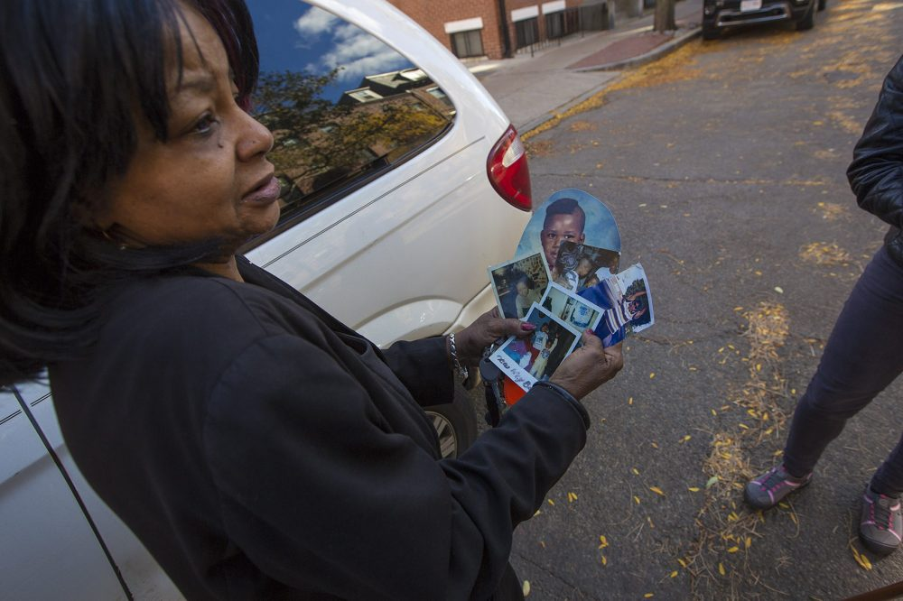 Hope Coleman holds old photos of her son Terrence, who was fatally shot by Boston police on Sunday morning. (Jesse Costa/WBUR)