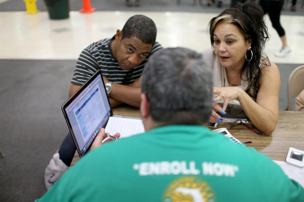 Jose Ramirez (left) and Mariana Silva speak with  Yosmay Valdivia, an agent from Sunshine Life and Health Advisors, as they discuss plans available from the Affordable Care Act at a store setup in the Mall of the Americas on Dec. 15, 2014 in Miami. (Joe Raedle/Getty Images)