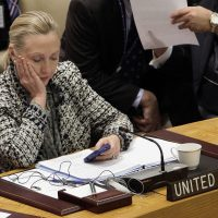 In this March 12, 2012, file photo, then-Secretary of State Hillary Clinton checks her mobile phone after her address to the Security Council at United Nations headquarters. (Richard Drew/AP)