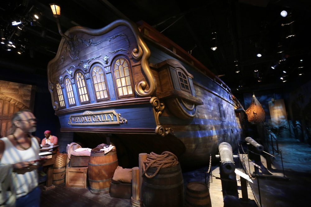 A museum visitor walks past a life-size replica of the hull of the pirate ship Whydah Gally, behind, at the Whydah Pirate Museum, in Yarmouth. (Steven Senne/AP)