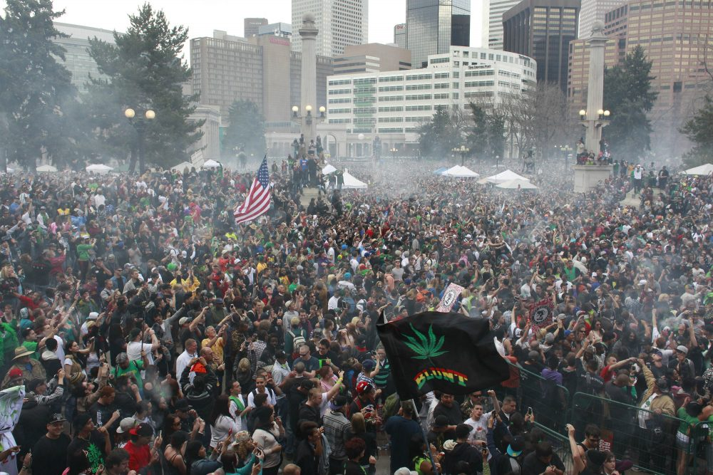 Let other states contend with the frenzied embrace of the new law, writes Susan E. Reed. Massachusetts can legalize marijuana after the party is over. Pictured: Members of a crowd numbering tens of thousands smoke marijuana at the Denver 4/20 pro-marijuana rally at Civic Center Park in Denver in 2013. (Brennan Linsley/AP)