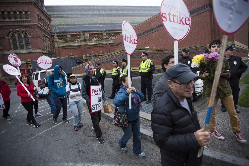 Police watch as Harvard University food service workers of the Local 26 UNITE HERE union picket peacefully outside of Memorial Hall Wednesday morning. (Jesse Costa/WBUR)