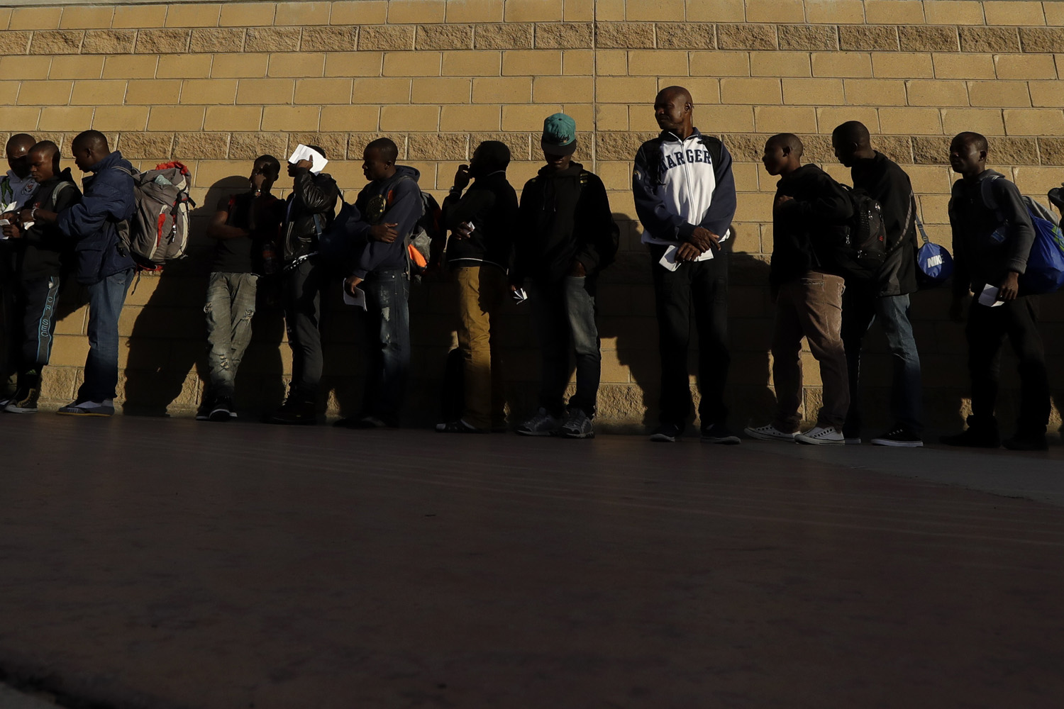 Haitian migrants line up as they wait to enter the U.S. border crossing, in Tijuana, Mexico. (Gregory Bull/AP)