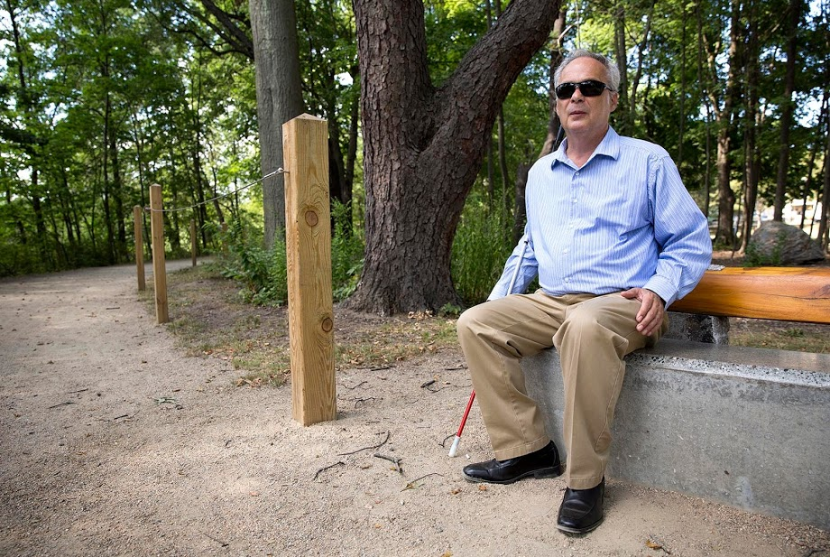Jerry Berrier sits in the Watertown Riverfront Park and Braille Trail, which was created by design firm Sasaki. (Robin Lubbock/WBUR)