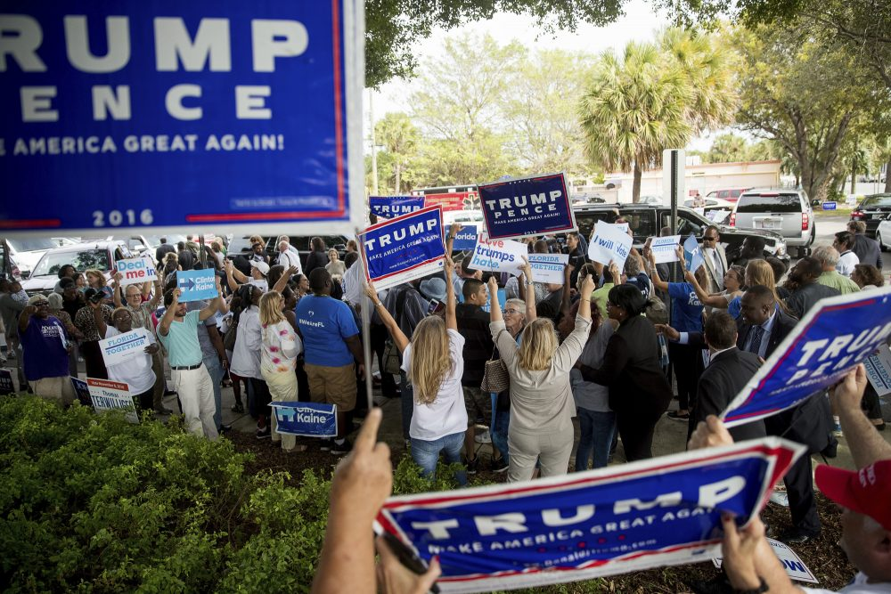 Supporters of Republican presidential candidate Donald Trump wave signs as Democratic presidential candidate Hillary Clinton greets supporters outside an early voting station in Pompano Beach, Fla., Sunday, Oct. 30, 2016. (Andrew Harnik/AP)