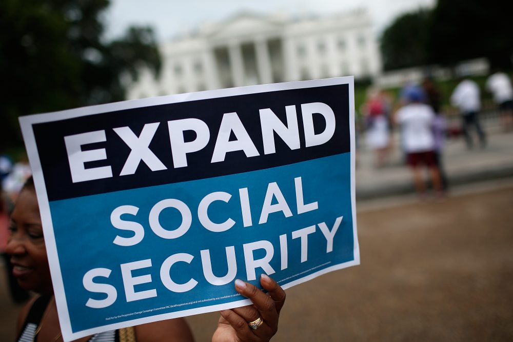 Activists participate in a rally urging the expansion of Social Security benefits in front of the White House in July 2015. (Win McNamee/Getty Images)