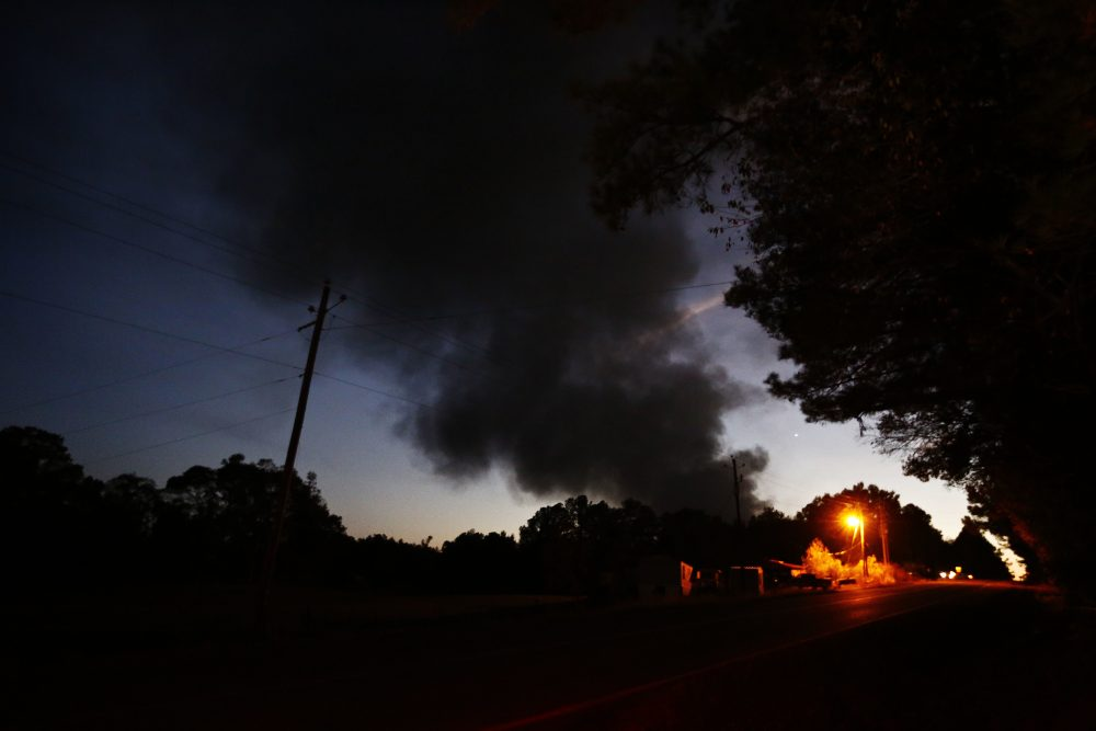 Light from a light pole shows a house near a plume of smoke from a Colonial Pipeline explosion, Monday, Oct. 31, 2016, in Helena, Ala. (Brynn Anderson/AP)