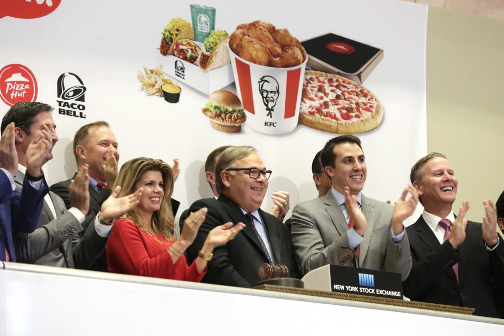 Yum Brands CEO Greg Creed, center, rings the New York Stock Exchange opening bell to mark the completion of the separation of Yum China Holdings, Inc. from Yum Brands, Tuesday, Nov. 1, 2016. (Richard Drew/AP Photo)