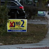 Next-door neighbors on Orchard Street in Watertown show their opinions about Question 2, one sign supporting the expansion of charter schools and one sign opposing it. (Jesse Costa/WBUR)