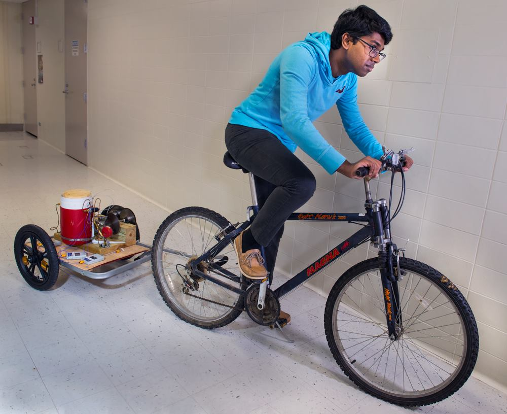 Anurudh Ganesan tests his invention, the VAXXWAGON, to see if it can be pulled by a bicycle. (Courtesy Anurudh Ganesan)