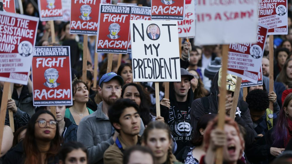 Protesters hold signs during a protest against the election of President-elect Donald Trump, Wednesday, Nov. 9, 2016, in downtown Seattle. (Ted S. Warren/AP)
