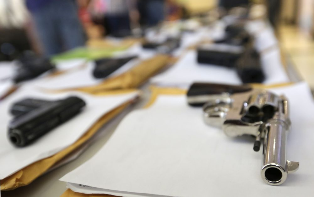 In this Monday, July 7, 2014, file photo, Chicago police display some of the thousands of illegal firearms they confiscated so far that year in their battle against gun violence in Chicago. (M. Spencer Green/AP)